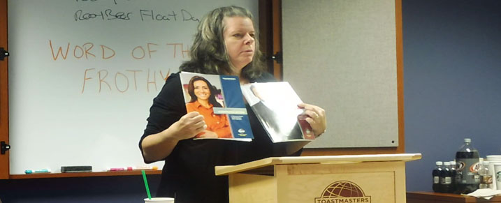 Spotlight member, Lisa Lewis shows two toastmaster manuals intended for new toastmasters to completed on National Root Beer Float Day.